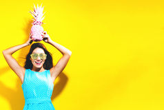 Happy young woman holding a pineapple Royalty Free Stock Photo