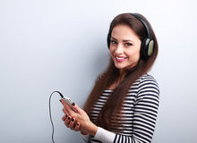 Happy young woman holding player and listening music in headphon Stock Image