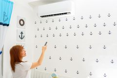 Happy Young Woman Holding Remote Control Relaxing Under The Air Conditioner. stock photography