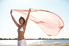 Happy young woman holding scarf on beach Royalty Free Stock Photography
