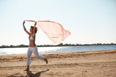 Happy young woman holding scarf on beach Stock Photos