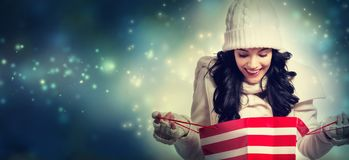 Happy young woman holding a shopping bag. In snowy night stock images
