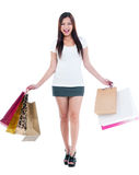 Happy Young Woman Holding Shopping Bags. Full length portrait of a happy Asian woman carrying shopping bags over white background Royalty Free Stock Photography