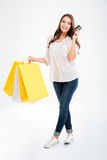 Happy young woman holding shopping bags and bank card stock photos