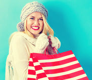 Happy young woman holding shopping bags. On a blue background Stock Photo