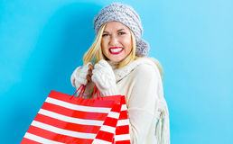 Happy young woman holding shopping bags. On a blue background Royalty Free Stock Images