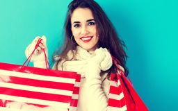 Happy young woman holding shopping bags. On a blue background Stock Image