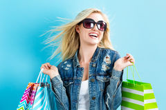 Happy young woman holding shopping bags. On a blue background Stock Images