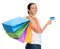 Happy young woman holding shopping bags and credit card Royalty Free Stock Image