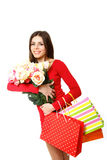 Happy young woman holding shopping bags and flowers on a white b. Happy young woman holding shopping bags and flowers on white background Royalty Free Stock Image