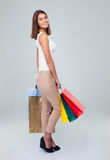 Happy young woman holding shopping bags. Full length portrait of a happy young woman holding shopping bags over gray background. Looking at camera Stock Images