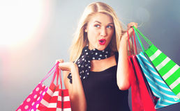 Happy young woman holding shopping bags. On a gray background Stock Photography