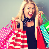 Happy young woman holding shopping bags. On a gray background Royalty Free Stock Images