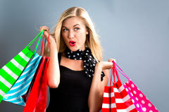 Happy young woman holding shopping bags. On a gray background Stock Images