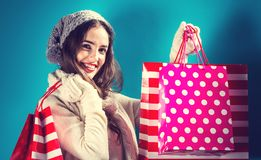 Happy young woman holding shopping bags. On a blue background Royalty Free Stock Photo