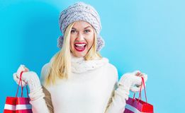 Happy young woman holding shopping bags. On a blue background Royalty Free Stock Photography
