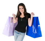 Happy young woman holding shopping bags, isolated. Beautiful young woman holding up shopping bags, happy and smiling, isolated on white background Stock Photos