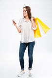 Happy young woman holding shopping bags and mobile phone. Full length portrait of a happy young woman holding shopping bags and mobile phone isolated on a white Royalty Free Stock Photo