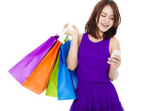 Happy young woman holding shopping bags and mobile phone Royalty Free Stock Images