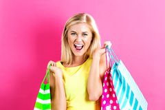 Happy young woman holding shopping bags. On a pink background Stock Images