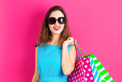 Happy young woman holding shopping bags. On a pink background Stock Photography