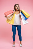 Happy young woman holding shopping bags staying on pink background Stock Photos
