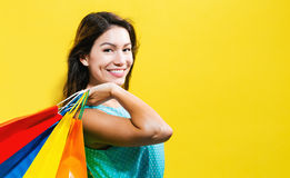 Happy young woman holding shopping bags. On a yellow background Royalty Free Stock Photography