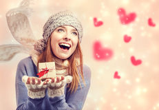 Happy young woman holding a small present box with hearts. Happy young woman holding a small present box with red hearts Royalty Free Stock Images