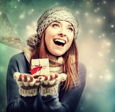 Happy young woman holding a small present box. In snowy night Royalty Free Stock Image