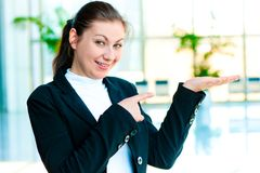 Happy young woman holding something on the palm of your hand and points a finger at her. On the background of the manager de-focus office interior Royalty Free Stock Image