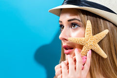 Happy young woman holding a starfish Royalty Free Stock Images