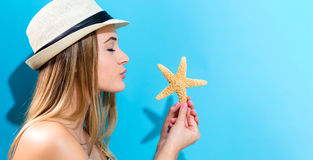Happy young woman holding a starfish Stock Images