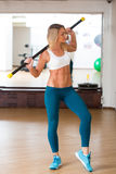 Happy young woman holding stick at fitness gym Royalty Free Stock Photography