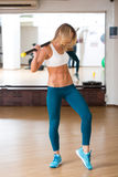 Happy young woman holding stick at fitness gym Royalty Free Stock Photos