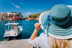 Happy young woman holding straw hat enjoying vacations in Assos village in front of emerald bay of Mediterranean sea. White boat and beautiful traditional royalty free stock image