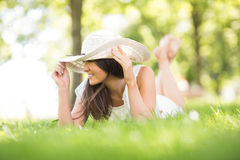 Happy young woman holding sun hat while lying on grassland Stock Images