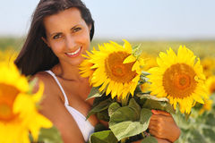 Happy young woman holding sunflowers. Beautiful girl holding a few sunflowers and feeling happy Royalty Free Stock Photography