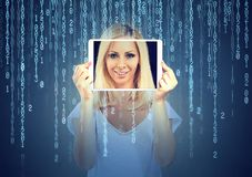 Happy young woman holding tablet with her face displayed on a screen isolated on binary code background. Happy woman holding tablet with her face displayed on a royalty free stock image