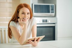 Happy young woman holding tablet and looking at camera royalty free stock photo