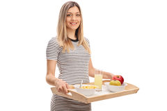 Happy young woman holding tray with bowl of cereal Stock Images