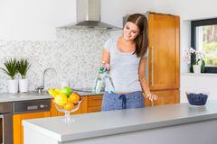 Happy young woman holding two bottles of water. IN KITCHEN Stock Photos