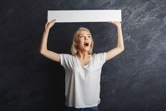 Young woman holding blank white banner. Happy young woman holding white blank banner over head. Excited girl showing paper sheet for sales advertisement, copy Royalty Free Stock Photo