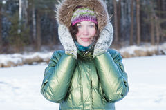 Happy young woman holding woolly mittens near her head in winter forest outdoors Stock Images