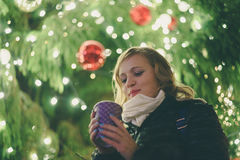 Happy young woman with hot beverage against cristmas tree Royalty Free Stock Photos