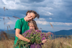 Happy young woman hugging daughter with a bouquet of wild flower. Happy young women hugging daughter with a bouquet of wild flowers on an alpine meadow while Royalty Free Stock Images