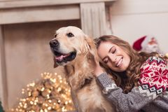 Young woman and dog at christmastime. Happy young woman hugging golden retriever dog at christmastime royalty free stock images