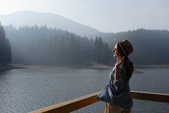 Free Happy Young Woman In Hat Enjoys Lake View In Mountains . Relaxing Moments In Forest. Freedom, People, Lifestyle, Travel Royalty Free Stock Photo - 165245155