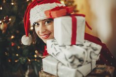Free Happy Young Woman In Santa Hat Holding Pile Of Gift Boxes At Golden Beautiful Christmas Tree With Lights In Festive Room. Happy W Royalty Free Stock Image - 125867336