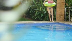 Happy young woman with an inflatable circle runs and jumps into the swimming pool in slow motion. 1920x1080 stock footage