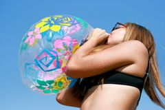 Happy young woman inflating the inflatable ball. Against blue sky Royalty Free Stock Photography